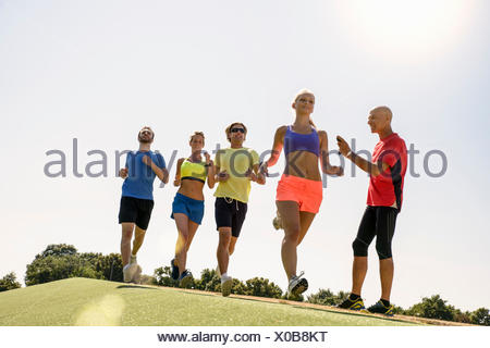 Group of runners being timed by trainer - Stock Photo