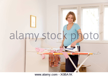 pregnant woman ironing baby clothes - Stock Photo