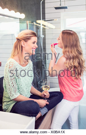 Smiling young woman sitting by sister applying lipstick in bathroom - Stock Photo