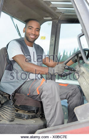 man in tractor at farm - Stock Photo