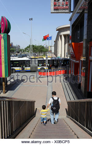 A father and son walk down stairs in the Qianmen district near Tiananmen Square. - Stock Photo