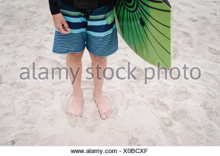 Boy on a sandy beach, wearing stripy blue swimming trunks, holding a bodyboard. - Stock Photo