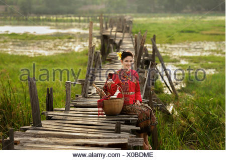 Portrait of Woman wearing traditional thai clothing sitting on bridge - Stock Photo