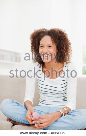 Smiling teenage girl sitting on sofa - Stock Photo