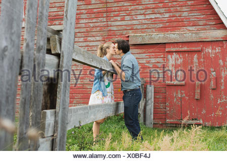 Couple kissing in front of barn. - Stock Photo