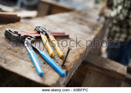 A reclaimed lumber workshop A person at a workbench and tools grippers and pliers lined up on a plank of wood - Stock Photo