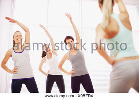 Women with arms raised in exercise class - Stock Photo