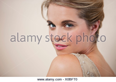 A young woman with her hair up, looking over her shoulder, close up - Stock Photo