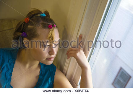 Young woman posing by a window. - Stock Photo