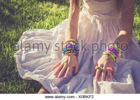 Little girl wearing loom bracelets and rings - Stock Photo