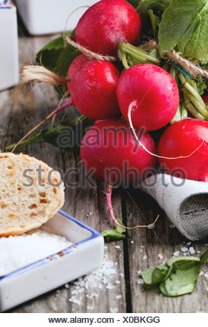Fresh wet radishes with sea salt and bread over old wooden table