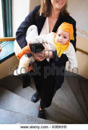 Mother and baby walking up the stairs, Sweden. - Stock Photo