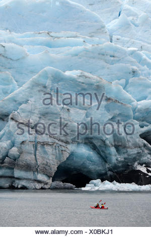 Red canoe (kayak) close to glacier front, Portage glacier, Alaska,USA - Stock Photo