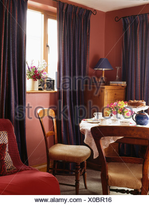 Blue curtains in pink cottage dining room with table set for tea - Stock Photo