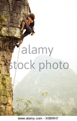 Female climber reaching out for a distant hold on overhanging limestone in China. - Stock Photo