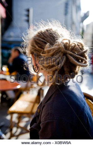 Woman with dreadlocks looking over shoulder - Stock Photo