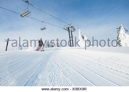 Mid-adult woman on ski slope under cable car - Stock Photo