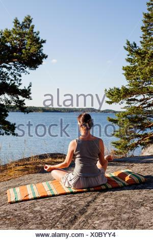 Sweden, Uppland, Runmaro, Barrskar, Rear view of woman meditating - Stock Photo