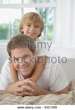 Man and young boy in bedroom playing - Stock Photo