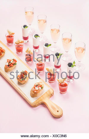 Catering, banquet or party food concept. Various snacks, brushetta sandwiches, gazpacho shots, desserts with berries in glasses on corporate event, ch - Stock Photo