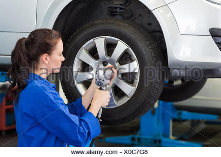 Mechanic adjusting the tire wheel - Stock Photo