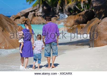 young family with two kids walking along tropical beach, Seychelles - Stock Photo