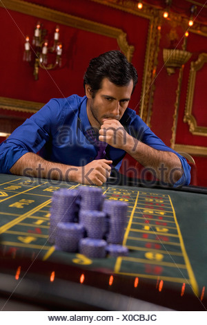 Anxious man looking at gambling chips in casino - Stock Photo
