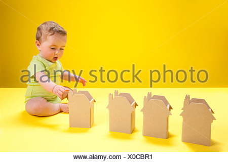 Baby boy playing with cardboard houses - Stock Photo