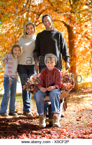 Family doing yard work in autumn - Stock Photo
