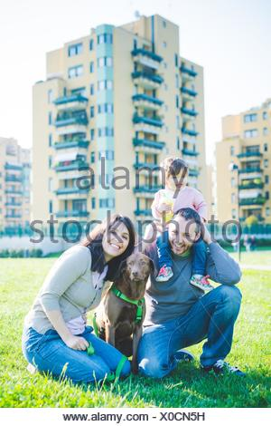 Portrait of mid adult couple with toddler daughter on shoulders in park - Stock Photo