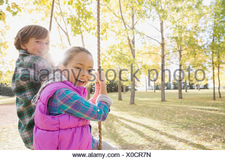 Siblings swinging at park - Stock Photo
