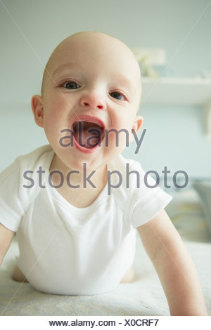 Baby boy crawling on bed - Stock Photo