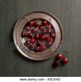 Plate of cherries on brown ceramic plate, against grey slate background - Stock Photo