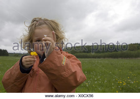 Field-landscape, girls, blond, rain-jacket, semi-portrait, spring, series, flower-meadow, meadow, people, child, 4 years, gaze camera, smiles, shows cheerfully, flowers, joy, childhood, freely, naturalness, weathers, rainy weather, clouds, outside, - Stock Photo