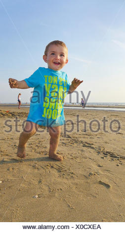little laughing boy wearing a T-shirt on a sandy beach, Netherlands - Stock Photo