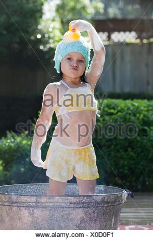 Portrait of girl standing in bubble bath in garden holding rubber duck on head - Stock Photo