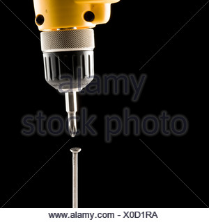 electric drill screwing a nail - Stock Photo