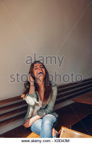 Carefree young woman sitting on bench in cafe - Stock Photo
