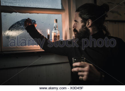 A man sitting alone in a room with a bottle of whisky and a glass, wiping condensation off window - Stock Photo