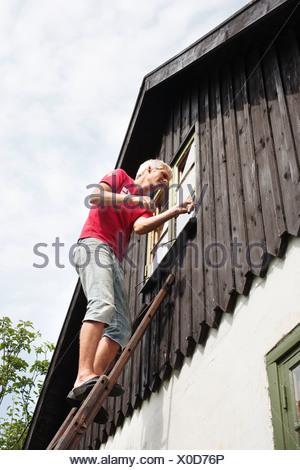 Man on ladder repairing window - Stock Photo