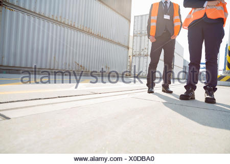 Low section of workers standing in shipping yard - Stock Photo