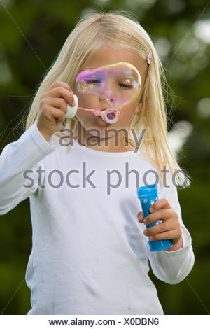 Blowing a giant soapbubble - Stock Photo
