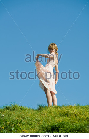 USA, San Francisco, California, young woman standing on grassy hill - Stock Photo