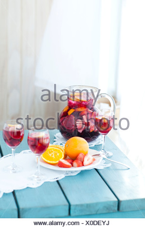 Glasses, jug and plate of fruits placed on wooden table - Stock Photo