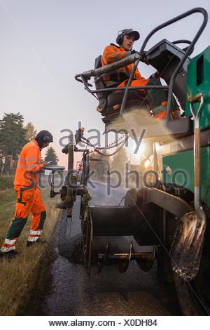Sweden, Narke, Two manual workers repairing road - Stock Photo