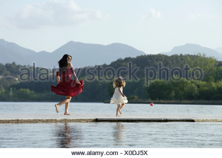 Woman and young girl skipping on dock - Stock Photo