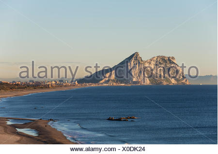 View of The Rock of Gibraltar and La Linea de la Concepcion as seen from the Mediterranean coast in the early morning light - Stock Photo