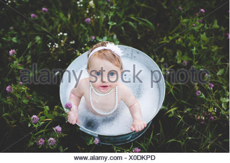 Overhead view of baby girl bathing in a tin bathtub in a wild flower meadow - Stock Photo
