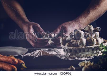 Cropped Image Of Chef Peeling Mushroom On Table - Stock Photo