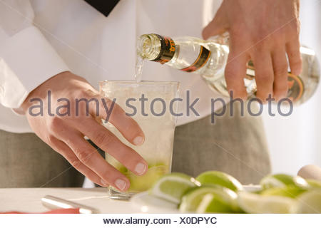 Barkeepers, detail, hands, cocktail, Caipirinha, prepare, glass, limes, ice, sugarcane schnapps, fill up, - Stock Photo